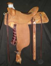 Lewis Roper Saddle made by Tyler Frecker. It has an inskirt rigging, ½ breed tooling with sunflowers, and brand. Also has elephant hide padded seat and semi square skirts.
