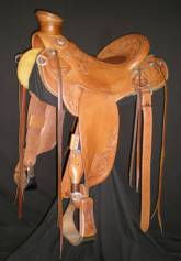 Ray Hunt Wade made by Kent Frecker; flat plate rigging, inlaid padded seat, and round skirts. Six panel tooling with swivel knife border. 3in. overshoe stirrups with cap. Made for a mule and has crupper rings, breeching rings, and saddle bag rings.