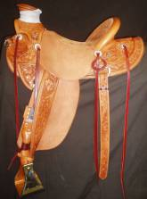 Wade Style Saddle. Half Breed Floral Tooling. Stirrup Leathers on Outside of Fenders. Eight Concho Style Flat Plate Rigging. Made by David Rigby