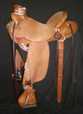 "Wade Saddle made for Reata Brannaman by Kent Frecker. It has a flat plate rigging, ½ breed design with California Poppies. Round Skirts, 5"" Stainless Steel Stirrups with cap. Custom made silver conchos and cantle plate by Lynn Tomlinson"