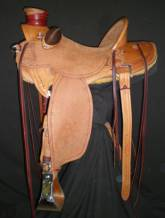 Wade Saddle made by Tyler Frecker; it has flat plate rigging, round skirts, and straight up cantle binding. ½ breed design with barb wire border.