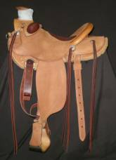 Wade Saddle made by Tyler Frecker; this saddle has an inskirt rigging, inlaid padded seat, and round skirts. All rough-out except on the swells and back of cantle.