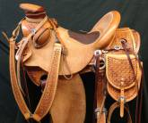 1/2 breed Geo-daisy pattern with inlaid padded elephant hide seat, beaver tail bucking rolls and matching saddles bags and martingal. Made by Karsten Frecker