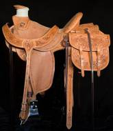 Half breed wade, wild rose and barbwire with barbwire on rough-out with matching saddle bags and martingale. Made by Kent Frecker