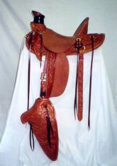 Half breed homestead floral with stirrup leathers on outside, eight conchos, and eagle beak tapaderos. Made by David Rigby